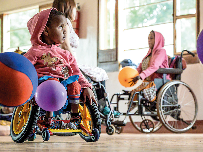 In den mitgebrachten Rollstühlen (l.) kommen die  Kinder in Haydom spielerisch in  Bewegung.
