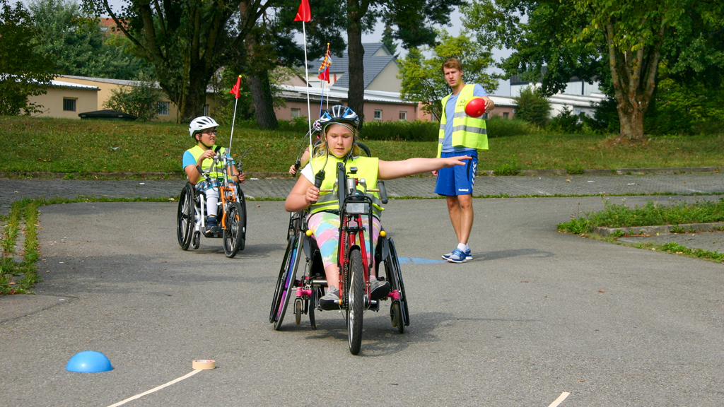 Mädchen im Rollstuhl mit Vorschnallbike beim Handbike Sicherheitstraining