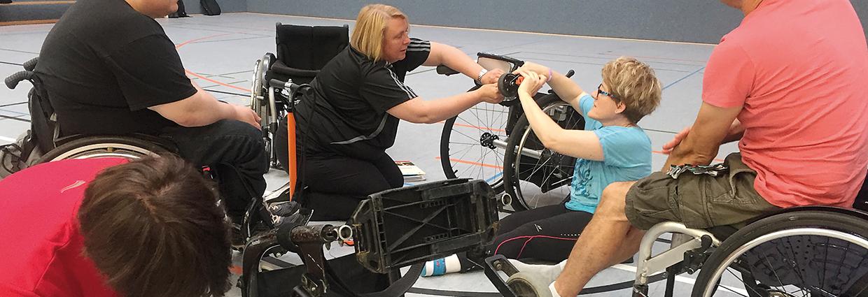 Übungsleiterinnen beim Schrauben am Rollstuhl